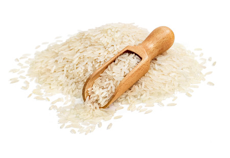 Wooden scoop and heap of long parboiled rice isolated on white background. Copy space. High resolution product. Healthy food concept