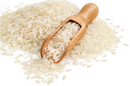 Close up of heap parboiled rice and wooden scoop isolated on white background. High resolution product. Healthy food concept Stock Photo