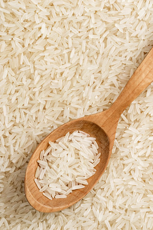 Rice in wooden spoon on background of long parboiled rice. Top view, close up, high resolution product. Healthy food concept