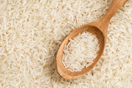 Close up of parboiled rice background with wooden spoon. Top view, high resolution product. Healthy food concept