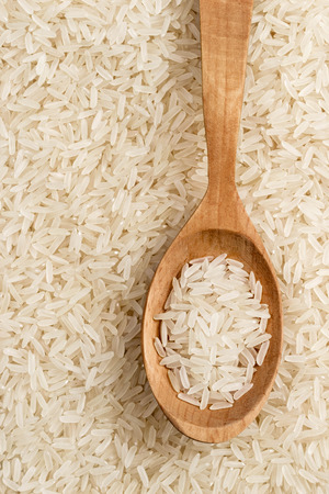 Parboiled rice background with wooden spoon. Top view, close up, high resolution product. Healthy food concept Stock Photo