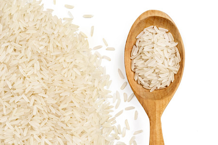 Close up of scattered parboiled rice and wooden spoon isolated on white background. Top view, copy space, high resolution product. Healthy food concept
