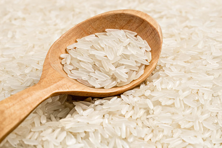 Long parboiled rice background with wooden spoon. Close up. High resolution product. Healthy food concept Stock Photo