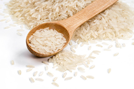 Heap parboiled rice and wooden spoon on white background. Close up, top view, high resolution product. Healthy food concept Stock Photo