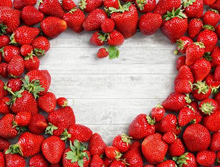 Hartvormig gemaakt van aardbei op witte houten achtergrond. Vruchten dieet concept. Detailopname. Bovenaanzicht. Hoge resolutie Stockfoto