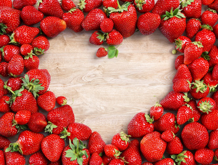 Heart shaped made of strawberry on wooden background. Fruits diet concept. Close up. Top view. High resolution Stock Photo