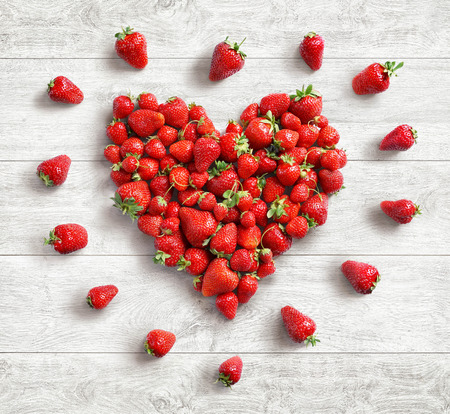 Heart symbol from strawberry on white wooden background. Fruits diet concept. Top view. High resolution product Stock Photo