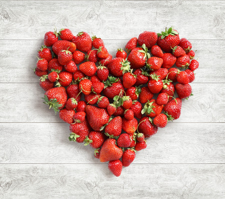 Heart shaped from strawberry on white wooden background. Fruits diet concept. Close up. Top view. High resolution Stock Photo