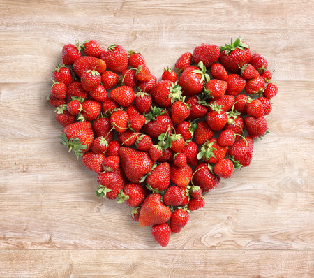 Heart shaped from strawberry on wooden background. Fruits diet concept. Close up. Top view. High resolution