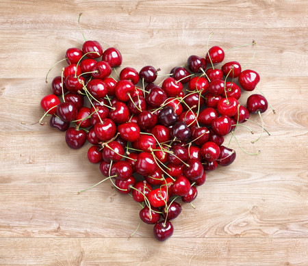 Heart shaped from cherry on wooden background. Fruits diet concept. Close up. Top view. High resolution