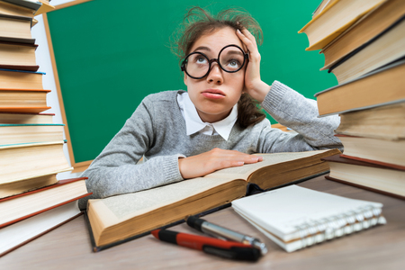 Exhausted or bored young student around a lots of books. Photo of student in classroom, education concept