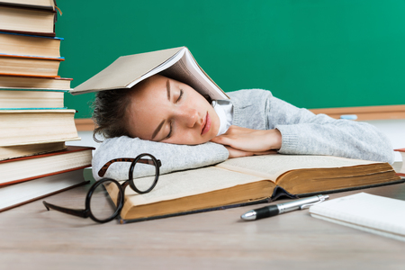 Tired student lies and sleep on the books. Photo of young girl in school. Back to school!