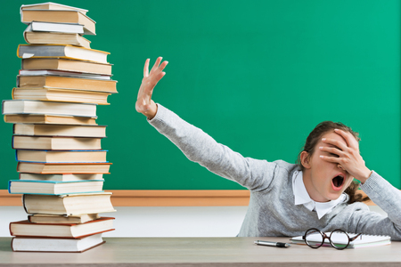 ショックを受けた学生は、たくさんの本に彼女の目を閉じます。学校でショックを受けた表情を持つ若い女の子の肖像画。新学期!