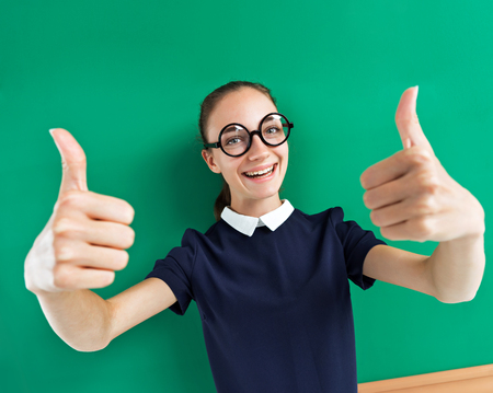 Happy young student showing her thumbs up. Photo of teen near blackboard, education concept