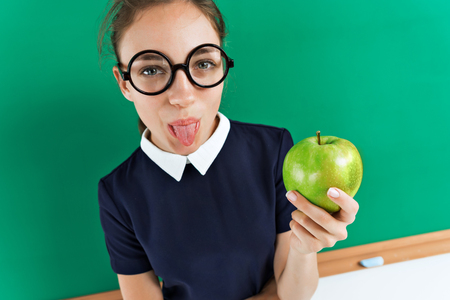 Emotional girl. Photo of sassy student shows tongue and holding an apple near blackboard, education concept