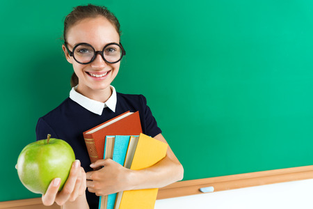 Smiling student hugging books and gives an apple. Photo of teen near blackboard, education concept