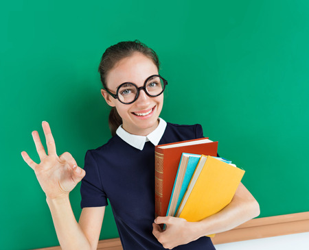 Smiling student showing okay gesture. Photo of teenager near blackboard, education concept Stock Photo