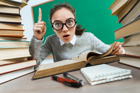 Did you know that?! Curious student reads a books. Photo of astonished young girl wearing glasses pointing finger up. Education concept