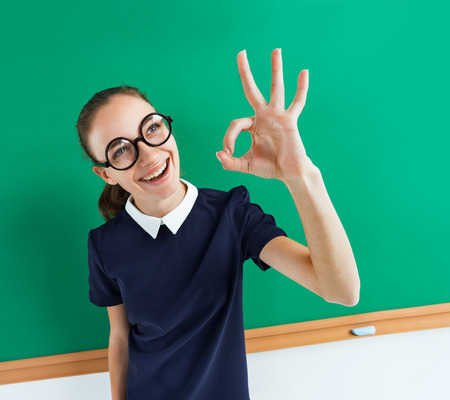 Happy young student showing okay gesture. Photo of teen near blackboard, education concept Stock Photo