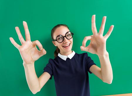 Back to school! Joyful young student showing okay. Photo of teen near blackboard, education concept. Stock Photo