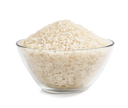 Heap of parboiled rice in glass bowl isolated on white background. Close up, high resolution product. Healthy food.
