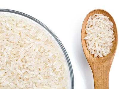 Healthy food. Close up of parboiled rice in glass bowl and wooden spoon isolated on white background. Top view. High resolution product.