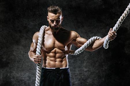 ロープでハンサムな男は。若い男に筋肉ボディとトップレスの写真。強度とモチベーション