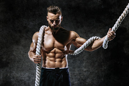 Handsome man with rope. Photo of young man with muscular topless body. Strength and motivation