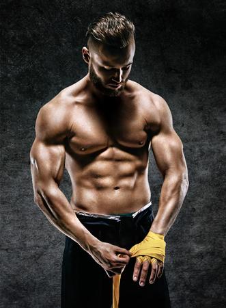 ボクサーは戦いの彼女の手袋を準備します。ストラップ筋肉の男の写真は暗い背景の手します。強さと動機。
