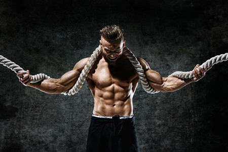 Muscular man with rope. Photo of man with perfect body after training. Fashion style