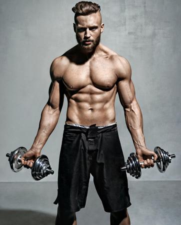 Sportieve man oefenen met halters. Foto van gespierde man op grijze achtergrond. Sterkte en motivatie.