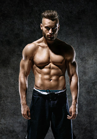 暗い背景にトレーニング後の完璧なボディを持つスポーティな男。強度とモチベーション