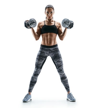Beautiful young woman in training pumping up muscles of the back and hands with dumbbells. Photo athletic woman with perfect body isolated on white background. Strength and motivation Stockfoto