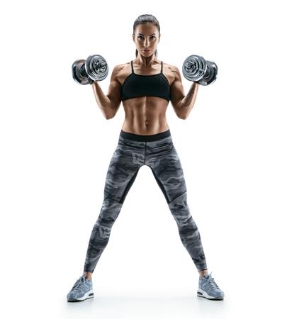 Mooie jonge vrouw in training pompen spieren van de rug en handen met dumbbells. Foto atletische vrouw met perfect lichaam geïsoleerd op een witte achtergrond. Sterkte en motivatie Stockfoto