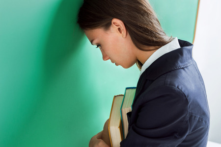 Sad student hiding face. Photo of young girl stands face to the blackboard. Side view. Back to school! Stock Photo
