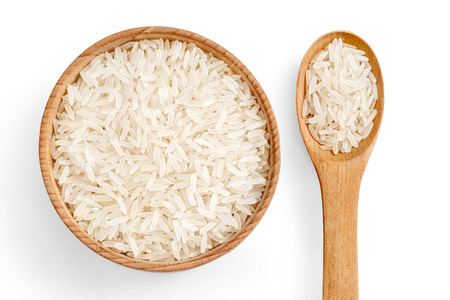 Healthy food. Parboiled rice in wooden bowl and wooden spoon isolated on white background. Top view. High resolution product. Stock Photo