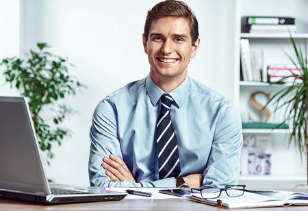 Uomo d'affari allegro seduto alla scrivania con le braccia piegate. Foto di successo uomo che lavora in ufficio. Concetto di affari