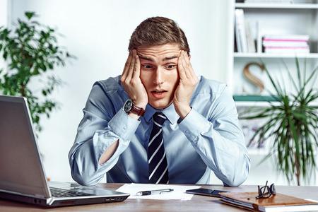 Gefrustreerde zakenman ontevreden zijn inkomsten. Foto van jonge man die in het kantoor werkt. Bedrijfsconcept Stockfoto