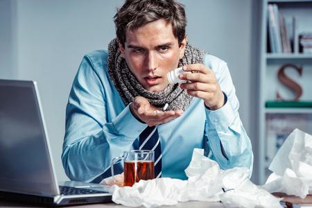 Pracownik chorobowy przyjmuje pigułki na grypę w biurze. Zdjęcie młodego człowieka cierpiący wirus grypy. Zdjęcie Seryjne