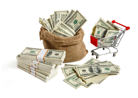 Bagful money  studio photo of a bag and shopping cart full of dollar bills Stock Photo