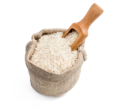 Close up of burlap sack with parboiled rice and scoop isolated on white background. Healthy food. High resolution product