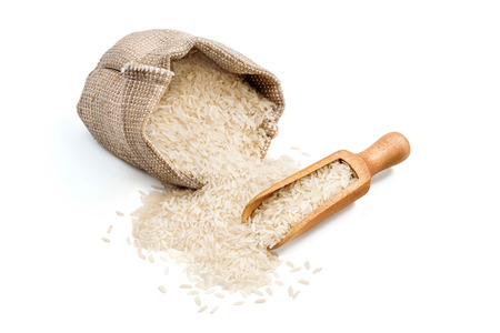 Parboiled rice scattered from burlap sack and wooden scoop isolated on white background. Healthy food. Close up, high resolution product