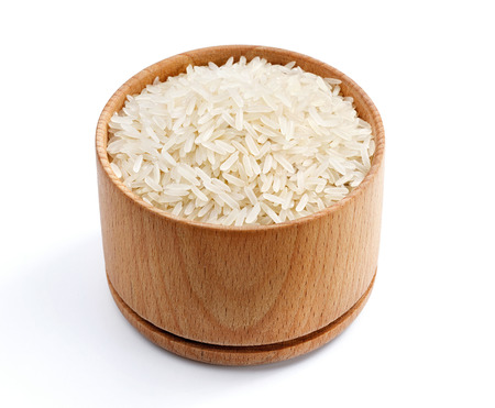 Healthy food. Parboiled rice in wooden bowl isolated on white background. Close up, high resolution product Stock Photo