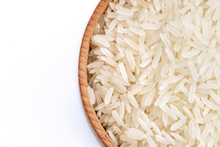 Healthy food. Wooden bowl filled parboiled rice on white background. Close up. Top view, high resolution product Stock Photo