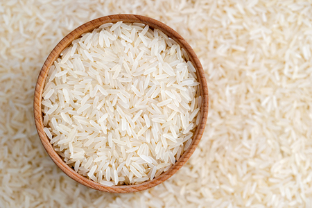 polished: Healthy food. Wooden bowl filled long parboiled rice on blurred background. Close up, top view, high resolution product.