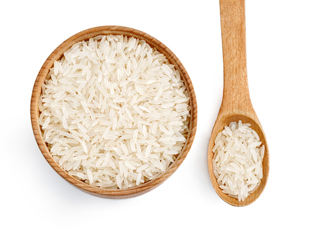 Parboiled rice in wooden bowl and wooden spoon on white background. Healthy food.Top view. High resolution product.
