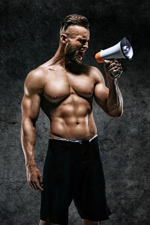 スポーティな男がメガホンに怒鳴っています。トレーニング後の完璧なボディを持つ若い男の写真。強度とモチベーション