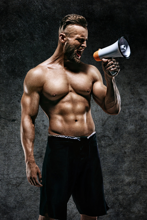 Sporty man shouting into the megaphone. Photo of young man with perfect body after training. Strength and motivation Stock Photo