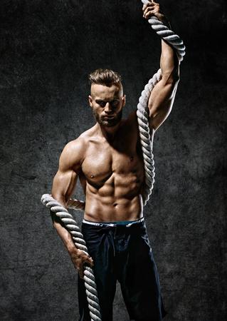 Sterke gespierde man met een touw. Foto van de man met een perfect lichaam na de training. Mode stijl