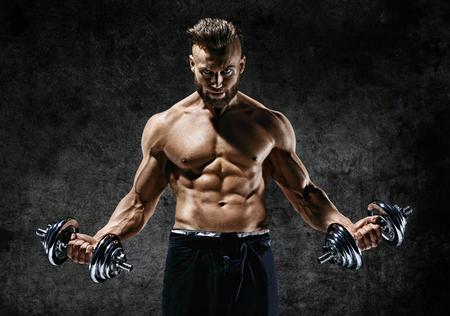 Fisiculturista poderosa fazendo os exercícios com halteres. Foto do macho forte com o torso despido no fundo escuro. Força e motivação.